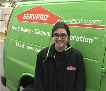 a woman standing in front of a green van