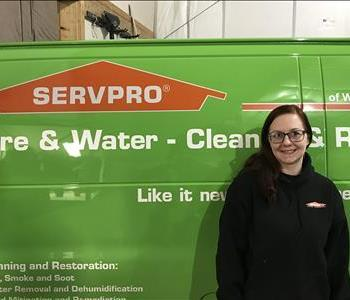 a girl in front of a green SERVPRO van