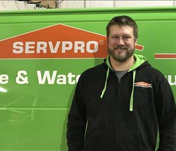 a man in front of a green SERVPRO truck