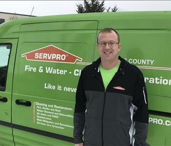 a man standing in front of a green van